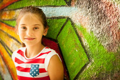 Young girl standing near graffiti wal on summer afternoon Stock Images