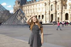 Young girl standing near Louvre Pyramid and smiling. stock image