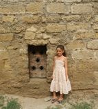 A young girl standing near medieval metal door in the limestone wall Royalty Free Stock Image
