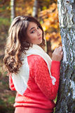 Young girl standing near the tree in beautiful autumn park Royalty Free Stock Photos