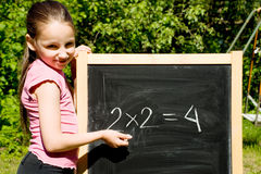 Young girl standing next to black slate. Solving praxis Royalty Free Stock Photography