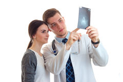 A young girl is standing next to a doctor in a white lab coat and he shows her an x-ray. Is isolated on a white background Stock Photo
