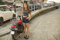 Young  girl standing outside his motorbike. Royalty Free Stock Image