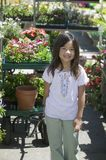 Young girl standing in plant nursery Royalty Free Stock Images