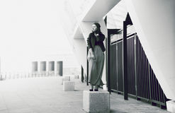 Young girl standing plinth like statue against urban landscape Royalty Free Stock Image