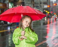 Young girl standing in rain with raincoat and umbrella stock image