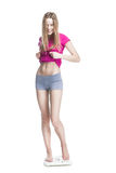 Young girl standing on the scales measuring weight Stock Images