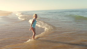 Young Girl Standing In Sea As Waves Break Stock Images