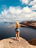 Young girl standing on sea rocks, enjoying freedom, feeling of female dignity. On the sky many clouds stock photography