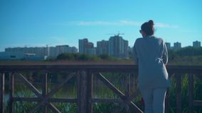 A young girl is standing on the shore of the lake against the background of the urban landscape and the blue sky. stock video
