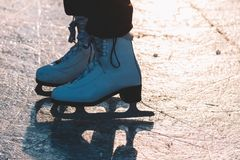 A young girl standing in skates on a frozen pond on ice. Nice soft sunset light. Detail of ice skates Stock Photography