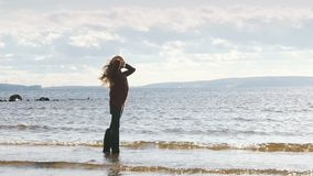 A young girl is standing and smilng in the river in rubber boots stock video footage