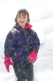 Young Girl Standing in Snow with Snow Falling. Little girl standing in the snow while snow is falling Stock Image