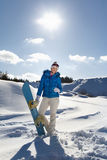 Young girl standing with snowboard. Pretty young girl standing with snowboard in her hand, sunny winter day Stock Image