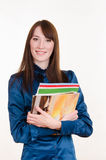 Young girl standing with a stack of magazines Royalty Free Stock Photos