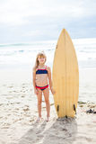 Young girl standing with surfboard on beach stock photography