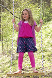 A young girl standing on a swing Stock Image