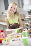 Young Girl Standing By Table Laid With Birthday Party Food Stock Photography