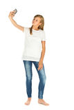 Young girl standing taking a selfie over white background Stock Photo