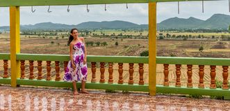 Young girl standing at temple overlooking rice paddy royalty free stock image