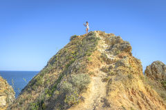 Young girl standing on top of a cliff Stock Images