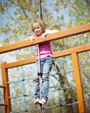 Young girl standing at top of rope and climbing frame Royalty Free Stock Photos