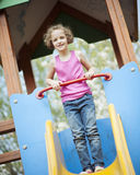 Young girl standing at top of slide in playground Royalty Free Stock Image