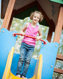 Young girl standing at top of slide in playground Stock Photography