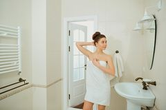 A young girl is standing in a towel in the bathroom. A young girl is standing in a towel by the mirror in the bathroom stock photos