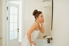 A young girl is standing in a towel in the bathroom. A young girl is standing in a towel by the mirror in the bathroom royalty free stock photos