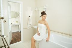 A young girl is standing in a towel in the bathroom. A young girl is standing in a towel by the mirror in the bathroom stock photography