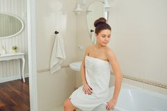 A young girl is standing in a towel in the bathroom. A young girl is standing in a towel by the mirror in the bathroom stock image