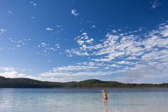 Young girl standing in the tranquil lake. McKanzie in Fraser Island and beautiful blue sky with some nice white clouds royalty free stock photography