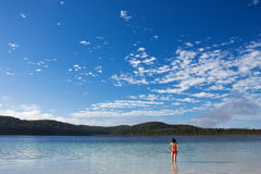 Young girl standing in the tranquil lake. McKanzie in Fraser Island and beautiful blue sky with some nice white clouds stock photography