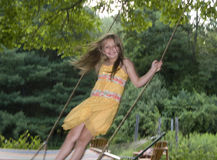Young girl standing on tree swing Stock Photos