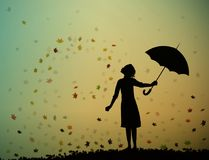 Young girl is standing under autumn leaves with an umbrella, Stock Photo