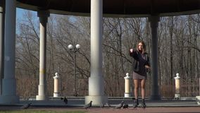 Young pretty girl feed pigeons in park. Young girl is standing under the dome and feeds wild pigeons. The girl spend her leisure time alone walking in the park stock video footage