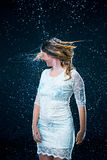 The young girl standing under running water Stock Image