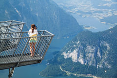 Young girl standing on the viewing platform Five Fingers. And observing with tourist binocular spectacular view of Alps and lake Hallstatter  see Royalty Free Stock Image