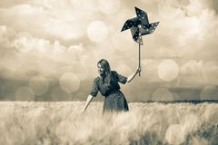 Girl is standing on a wheat field with pinwheel royalty free stock image
