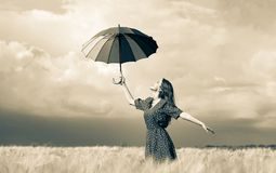 Girl is standing on a wheat field with umbrella stock photography
