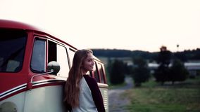 A young girl standing y a car on a roadtrip through countryside. A young girl stabding by a car on a roadtrip through countryside. Slow motion stock video footage