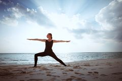 Young girl standing in yoga warrior asana on dreamlike beach on summer vacation Royalty Free Stock Photos