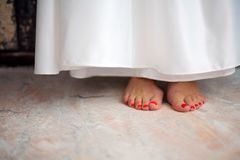 A young girl stands barefoot on the floor. White dress royalty free stock photo