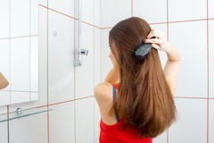 A young girl stands in the bathroom and combing their hair Stock Photography