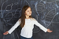 Young girl stands at the blackboard Stock Images