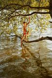 Young girl stands on a branch of a tree over the water of a river and splashes her foot stock photography