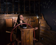 A young girl stands at the helm of the ship and looks into the d. Istance, escape the room game concept royalty free stock photography