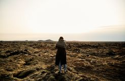 A young girl stands with her back and takes pictures of the landscape. royalty free stock photography
