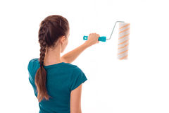 A young girl stands with her back to the camera holding a roller for painting Stock Photo
